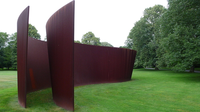 "On the Riggios's Brigehampton front lawn, Richard Serra's ""Sidewinder."""